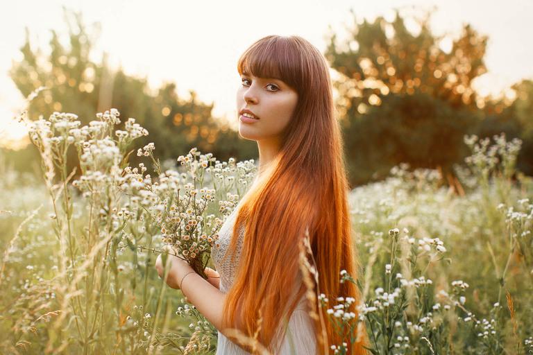 ritratto di ragazza con capelli rossi al tramonto in un campo di fiori
