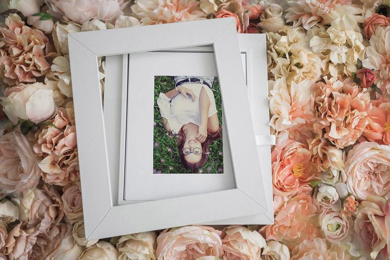 reveal box poggiata su uno sfondo di fiori finti dalle tinte tenui contenente un ritratto di una giovane ragazza sorridente distesa in un prato