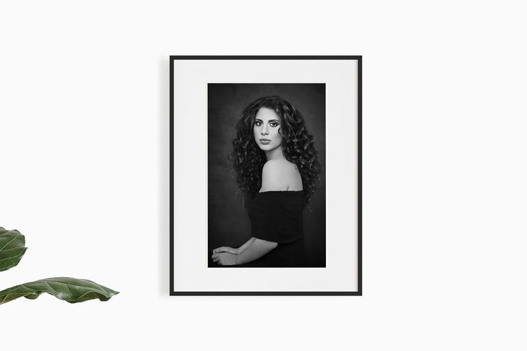 parete bianca con il ritratto incorniciato di ragazza riccia mora con vestito nero