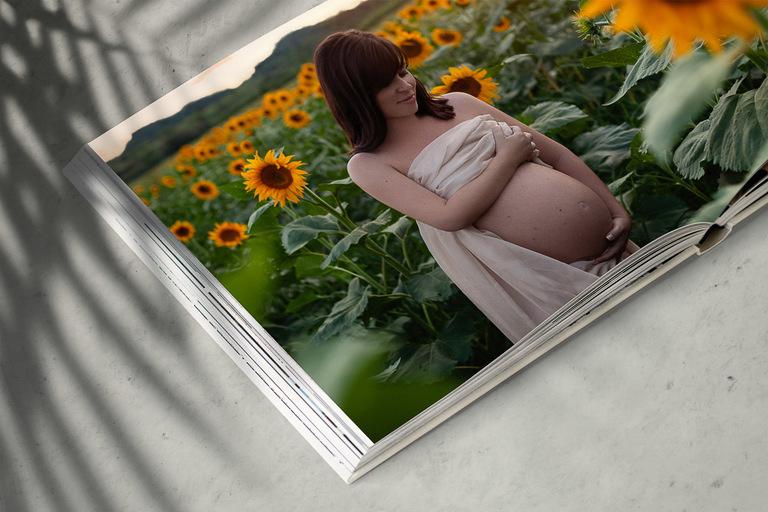 album fotografico con ritratto di donna incinta al tramonto in un campo di girasoli