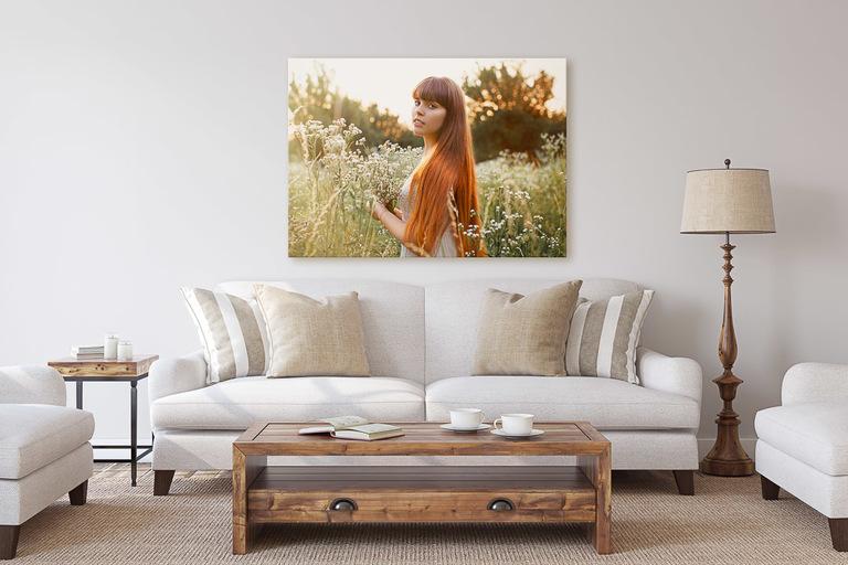 wallart appeso in salotto sopra un divano bianco raffigurante il ritratto di una giovane ragazza con i capelli lunghi e rossi in un campo di fiori selvatici